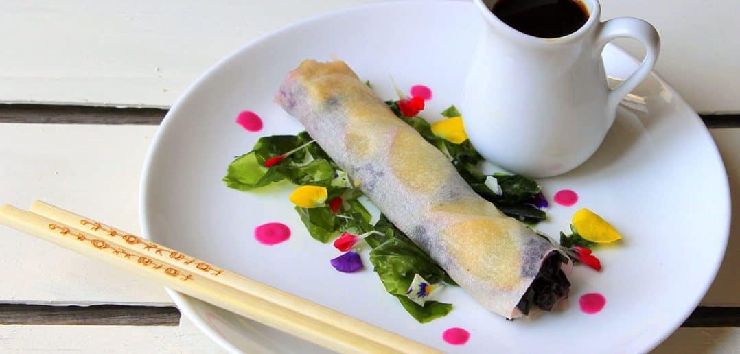 Piatto con Involtini di sfoglia di riso al pesce spada affumicato, alghe nori e mango con crema di avocado e menta.